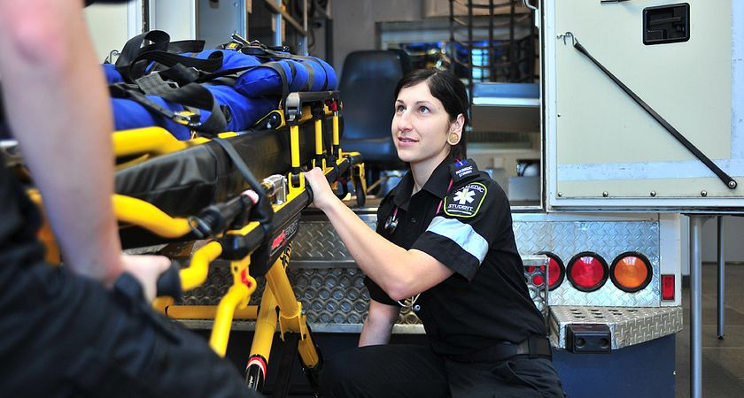 Female paramedic student crouched down by a stretcher with a dummy patient as she looks up to her peers