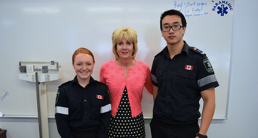 picture of two centennial college paramedic program students who saved a life at a marathon with president ann buller