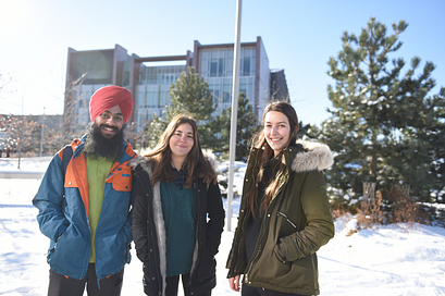Picture of three Led young College students in winter wear standing in front of a snow Progress Campus