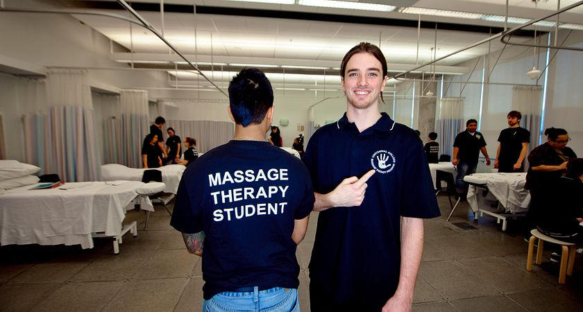 Massage therapy student points to the logo in front of his shirt, while his peer faces back of camera with his shirt saying Massage Therapy Student