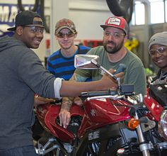 Motorcycle students clustered around a vehicle in our auto lab