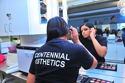 Female esthetician student puts on mascara behind the camera as her front side shows on the mirror