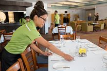Picture of a female student in one of Centennial College's hospitality programs setting a table in a restaurant.