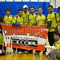 The Centennial Colt Cricket team holds the champions banner and poses for a team photo with their coach inside the gymnasium