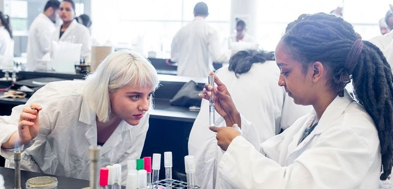 picture of centennial college students in a lab looking at a liquid in a test tube