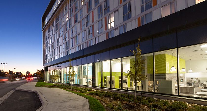 picture of the Centennial College Culinary Arts Centre building from the outside at dusk looking in at the kitchen facilities