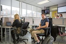 picture of a Centennial College student smiling and working in a computer lab at the Story Arts Centre
