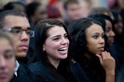 Female HYPE student laughing in a group with other students around her.