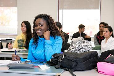 picture of a Led young College Business - Supply Chain and Operations program student smiling in class