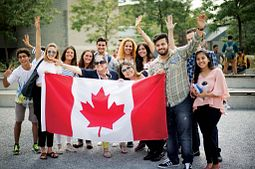 Picture of Centennial College International Education students holding a Canadian flag cheering