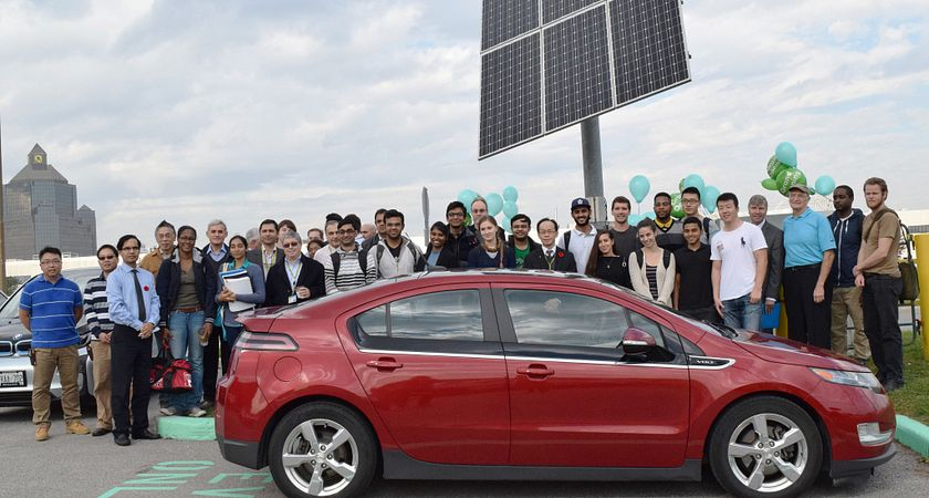 Picture of centennial college students and faculty at the off-grid electric vehicle charging station and an electric vehicle