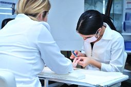Female esthetician student wears mask and files the fingernail of her peer in the esthetician clinic at Morningside campus