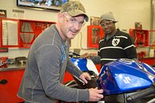continuing education students working on a motorcycle