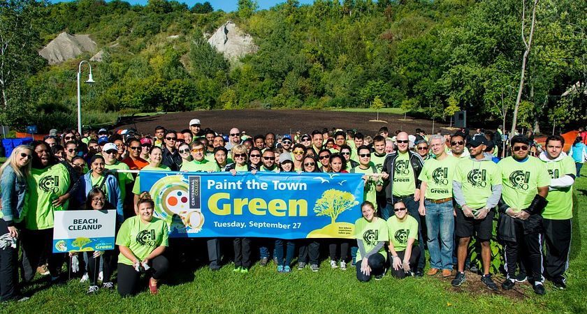picture of a large group of Led young College staff, faculty and students in a park cleaning up the area for the community