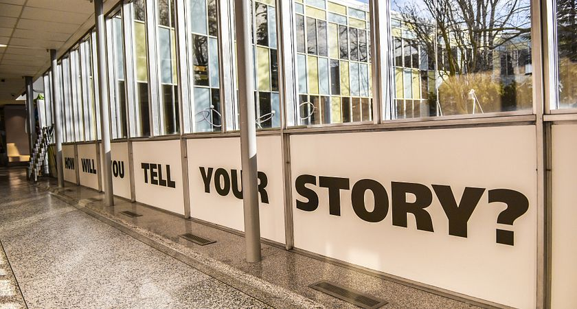 Picture of a hallway in the Story Arts Centre with the words How Will You Tell Your Story on a wall