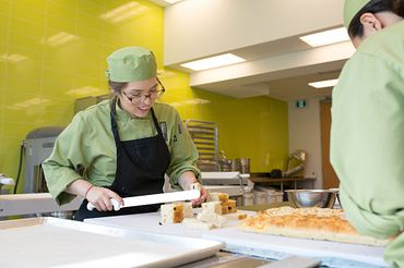 picture of a Centennial College Baking and Pastry Arts program student cutting bread in a kitchen