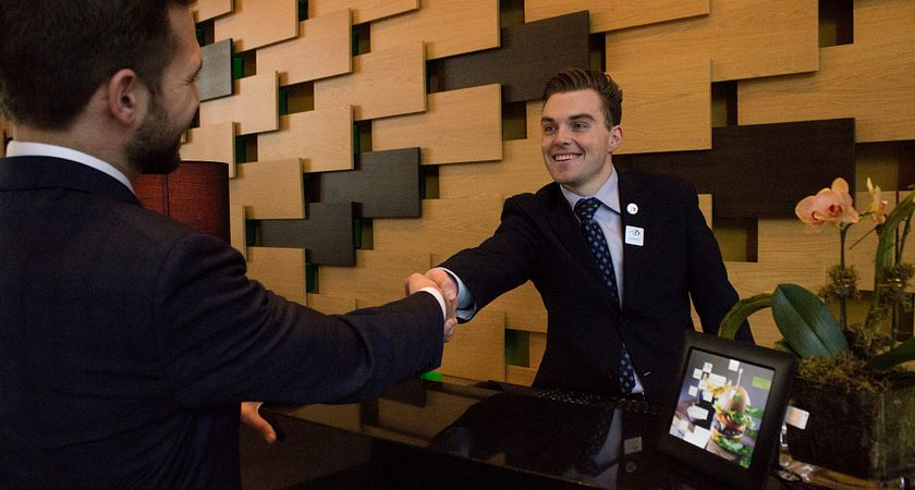 picture of a Centennial College Hospitality Hotel Operations Management program student working as a concierge speaking with a guest