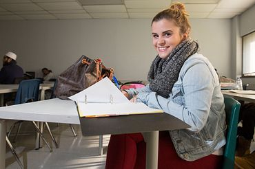 picture of a Centennial College Community and Justice Services program student in class at a desk smiling