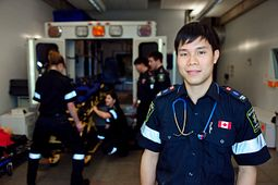 Picture of male paramedicine student standing outside the back of an ambulance.