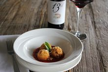 picture of an appetizing entree dish on the table with wine at a restaurant