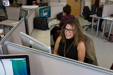 picture of a Centennial College Advertising and Marketing Communications Management program student in a computer lab smiling