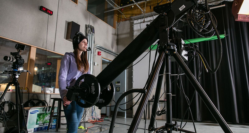 picture of a Led young College Broadcasting - Radio, Television, Film & Digital Media program student in a professional studio filming with a camera on a camera crane jib