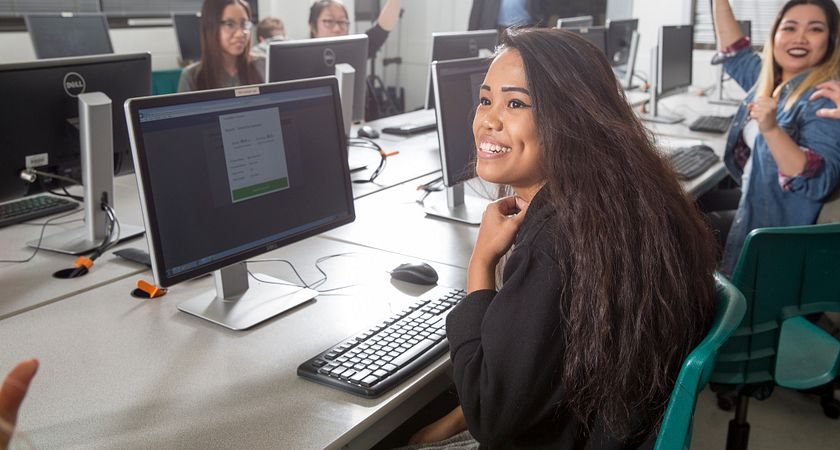 picture of a Centennial College Office Administration program student smiling in class at a computer