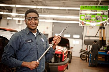 Picture of an automotive student in our labs working on a car