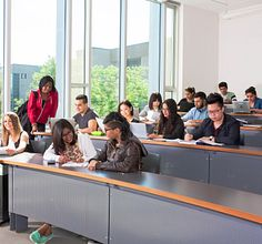 A group of students at their desks in a college classroom