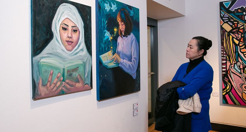 Picture of female guest observing student art work at the Toronto Centre for the Arts Gallery