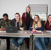 Picture of smiling Centennial College students in class with their instructor