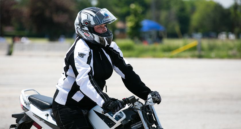 picture of a Centennial College Motorcycler and Powersports Product Repair Techniques program student riding on a motorcycle in a parking lot