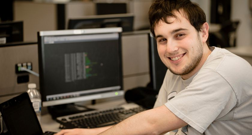 Photo of a male Information and Communication Engineering Technology student turning to the camera as his hands lay on the keyboard of his laptop