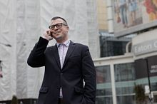 picture of a Centennial College Public Relations Corporate Communications program graduate wearing business professional and talking on a cellphone outside in a city setting