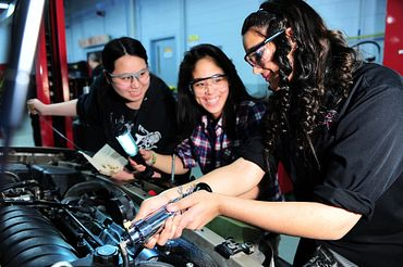 Picture of three female student repairing an automobile