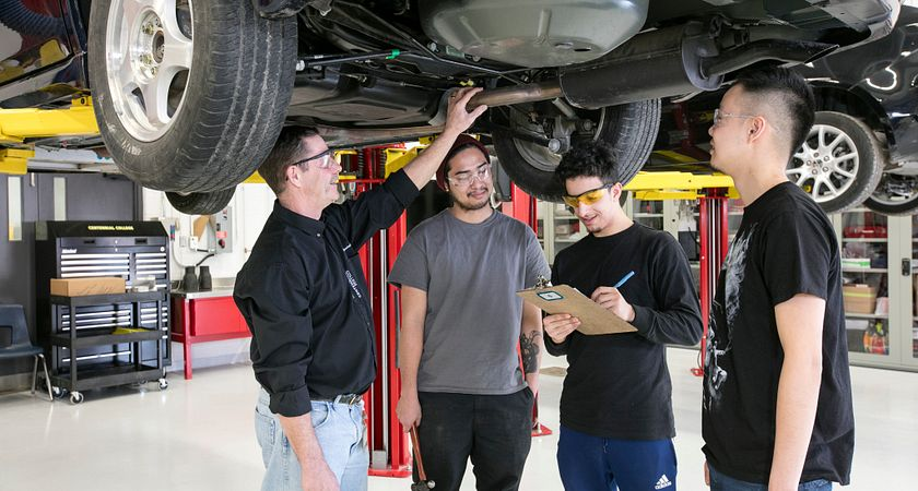 picture of Centennial College Auto Body Repair Techniques program students and faculty member looking under a car on a lift