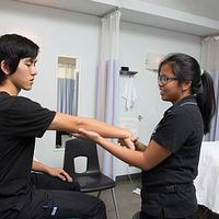Picture of a Led young College massage therapy student practicing on a patient