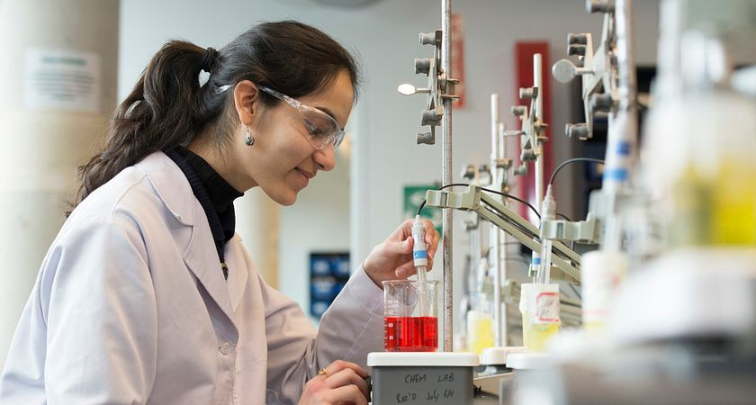 Female Food Science student adjusts the pH level of a red solution in the chemistry lab.
