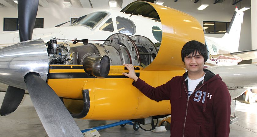 picture of centennial college student standing beside airplane