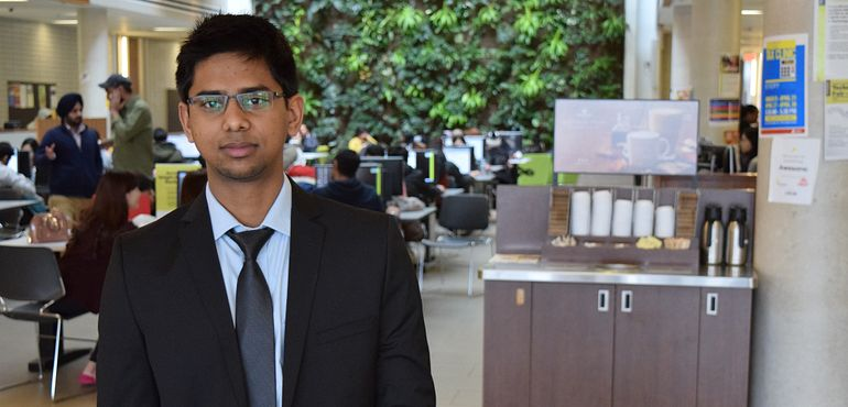picture of a centennial college student standing in the progress campus library dressed in business professional