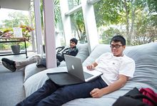 picture of centennial college students sitting on bean bag chairs booking their assessment test online