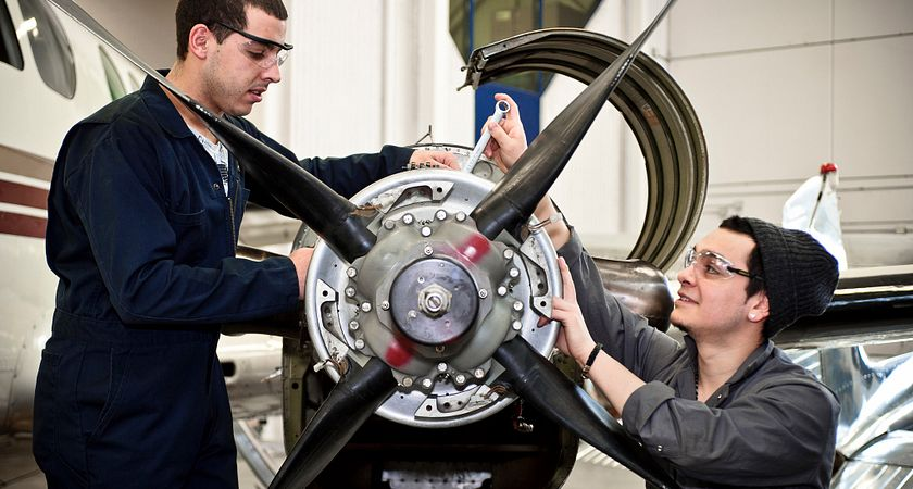 picture of two Centennial College students working on an airplane engine