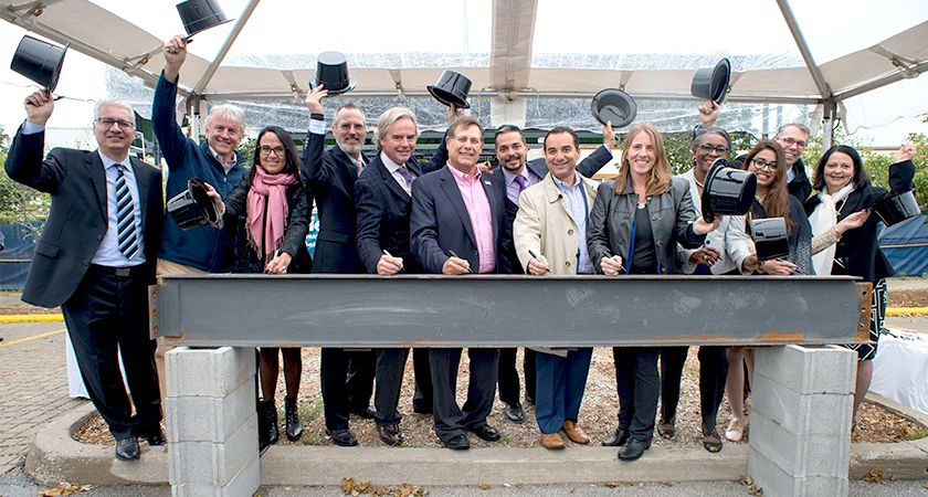 Picture of Students, staff, dignitaries, and guests were on hand to sign a steel I-beam before it was hoisted and incorporated into the new hangar that forms the central feature of the rejuvenated former headquarters of de Havilland Canada