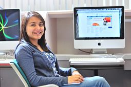 Picture of female Aboriginal student on a chair with a Mac computer on the background with the School of Communications Media and Design webpage in the background