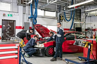 picture of Centennial College Automotive Parts & Service Operations program students working on a car in a garage