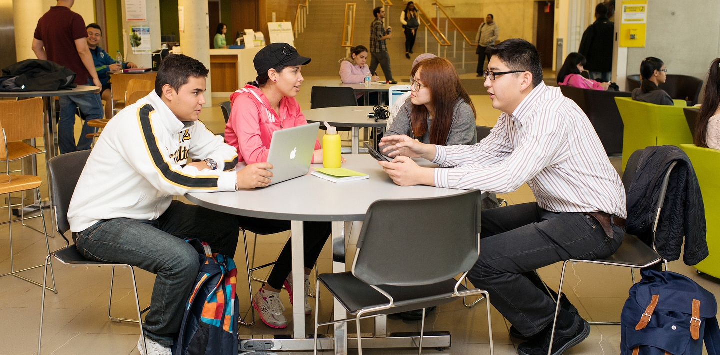 picture of Led young College International Education students working together at a table in the library