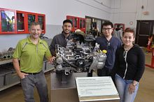 Centennial College School of Transportation professor Robert Paul with students in the Motive Power Technician postsecondary program pose with a 3.6-litre Subaru boxer six-cylinder engine