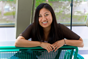 Picture of a Led young College International Education Student sitting on a bench at progress campus smiling