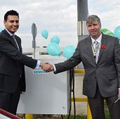 Picture of centennial college's dean of school of engineering technology and applied science patrick kelly and azeem qureshi from grasshopper solar shaking hands at the off-grid electric vehicle charging station ribbon cutting ceremony