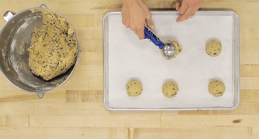 picture of hands scooping cookie dough on to a baking tray
